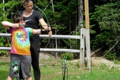 CIT helping camper with archery